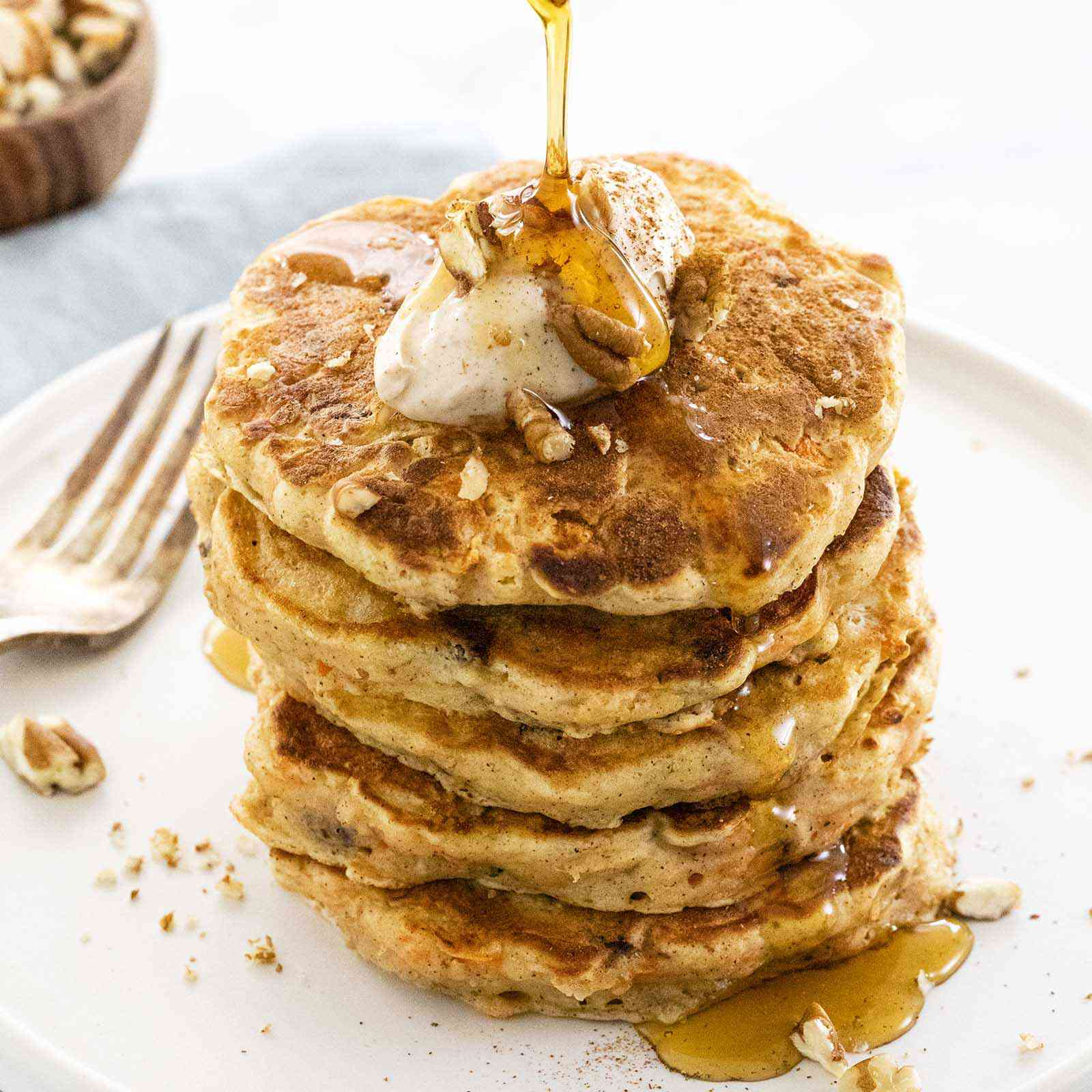 A tall stack of buttermilk carrot cake pancakes is topped with cream cheese topping and chopped pecans. Syrup is being poured over the top and dripping down the side of the pancakes. A wood bowl of chopped pecans is above the plate and a fork is on the left side of the plate.