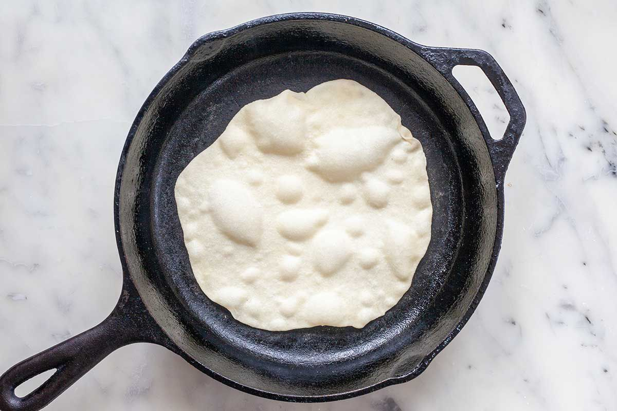 Easy homemade flour tortilla cooking in a cast iron skillet. It is pale and bubbly.