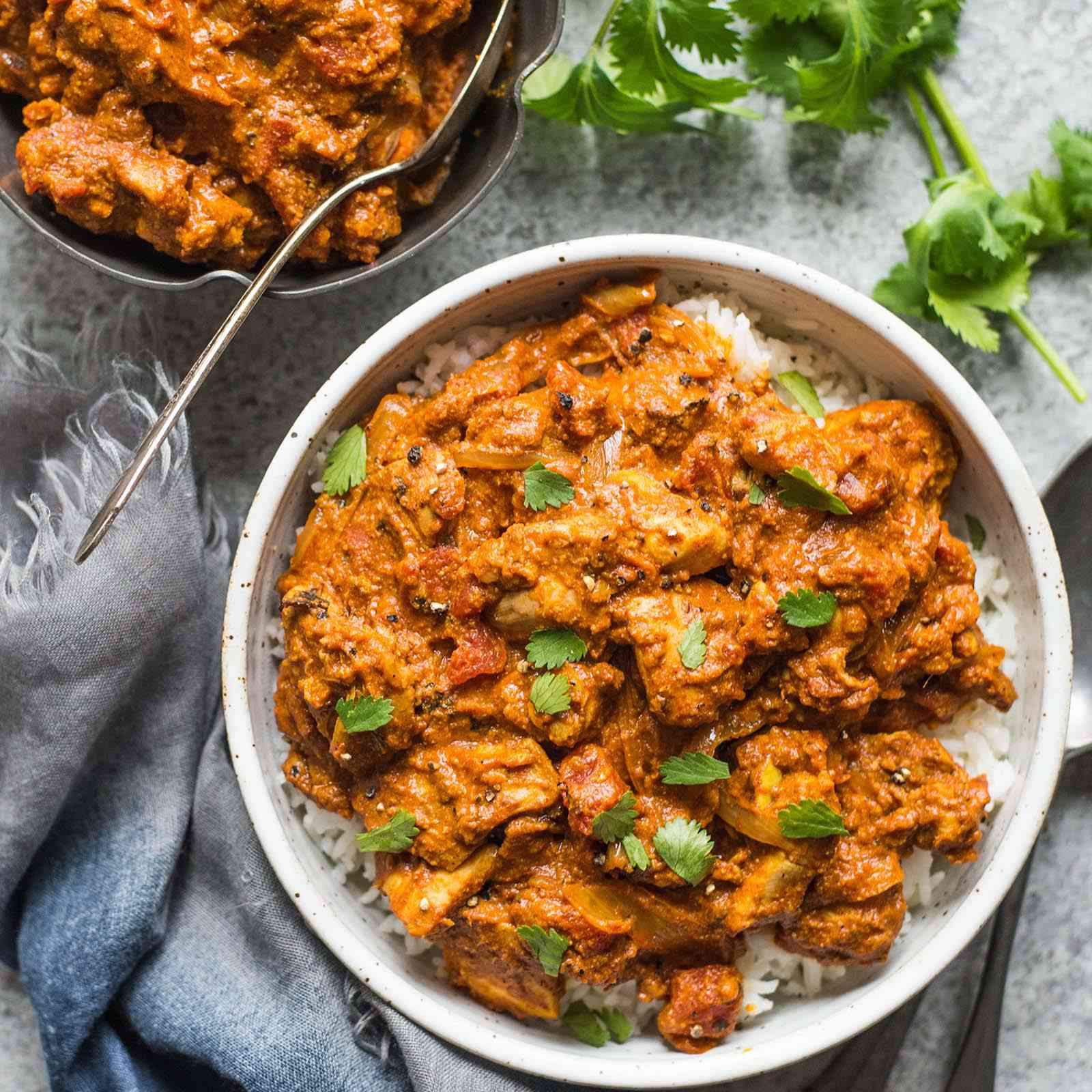 Chicken Tikka Masala Recipe in a bowl with rice and cilantro sprigs