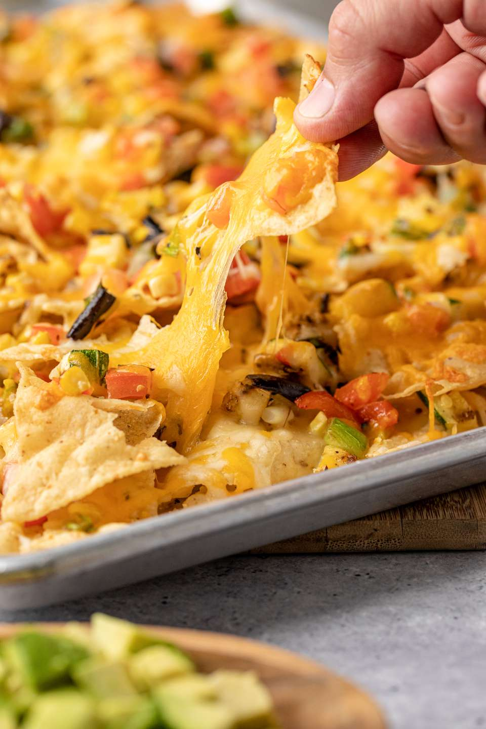 Picking up a chip from a pan of easy grilled vegetable nachos.