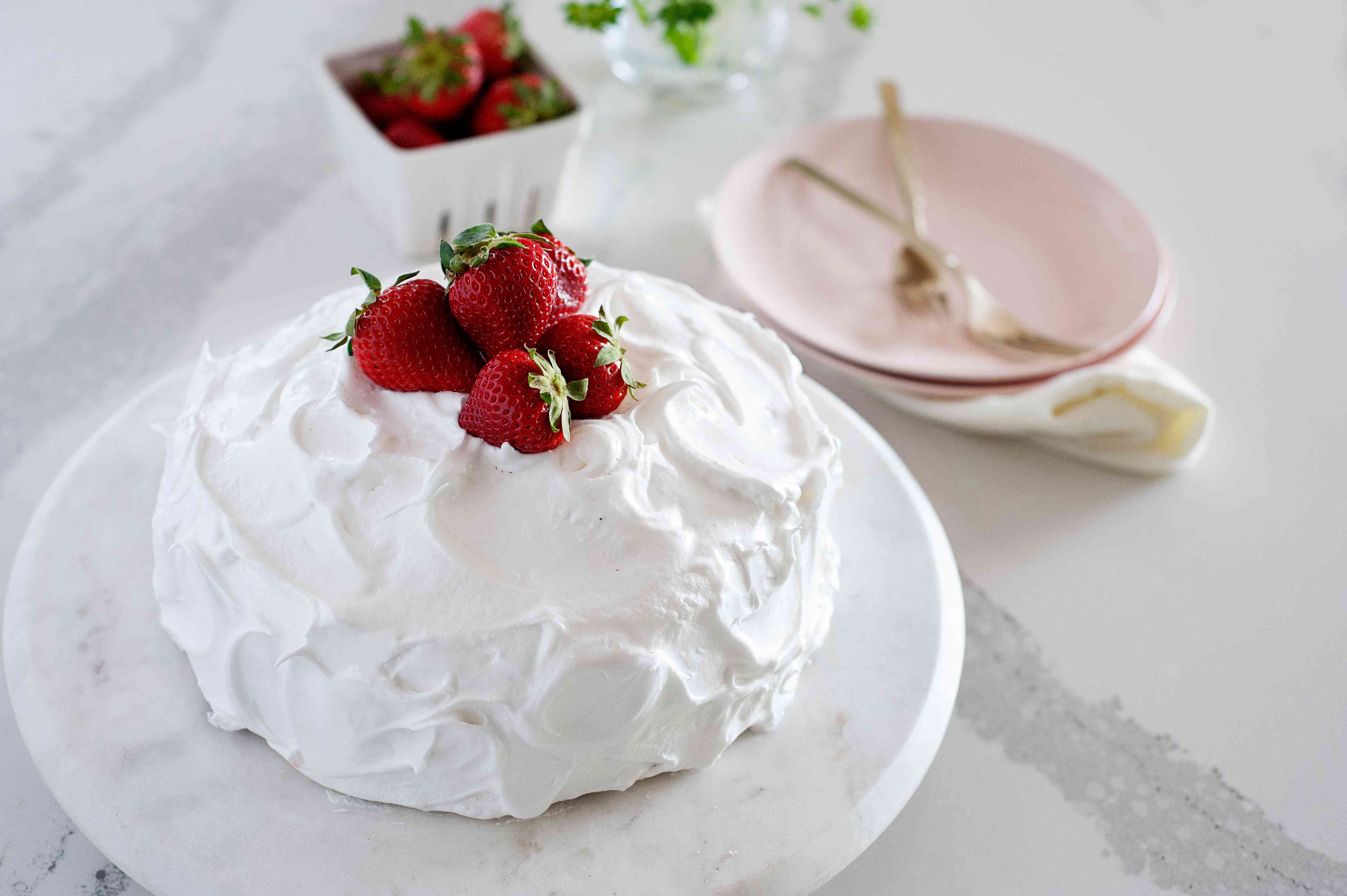 Grandma's Old-Fashioned Strawberry Cake on a cake stand and topped with strawberries.