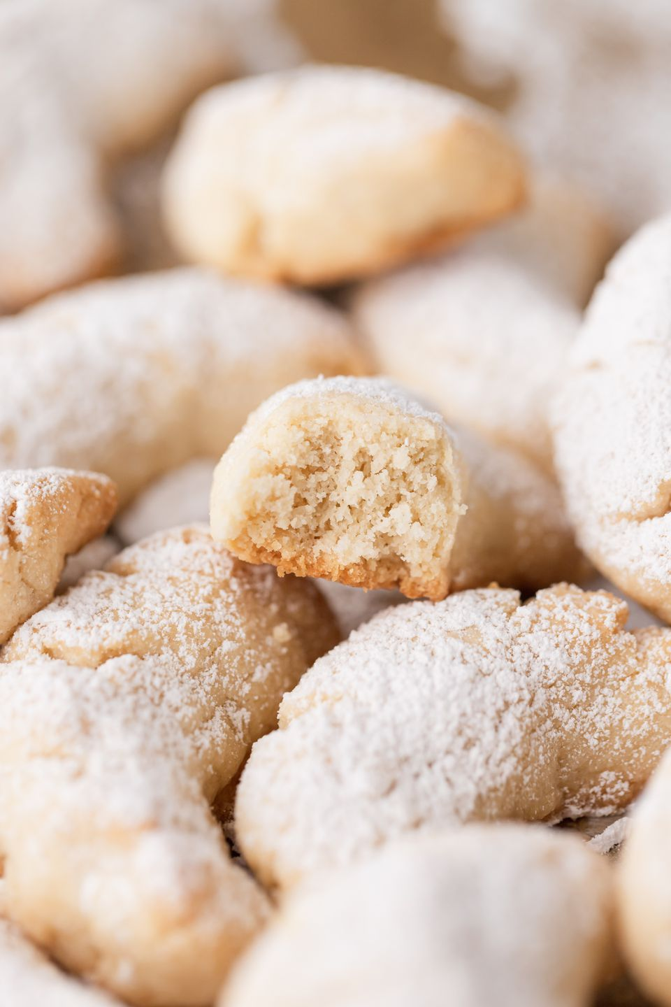 Side view of a close up of almond crescent cookies.