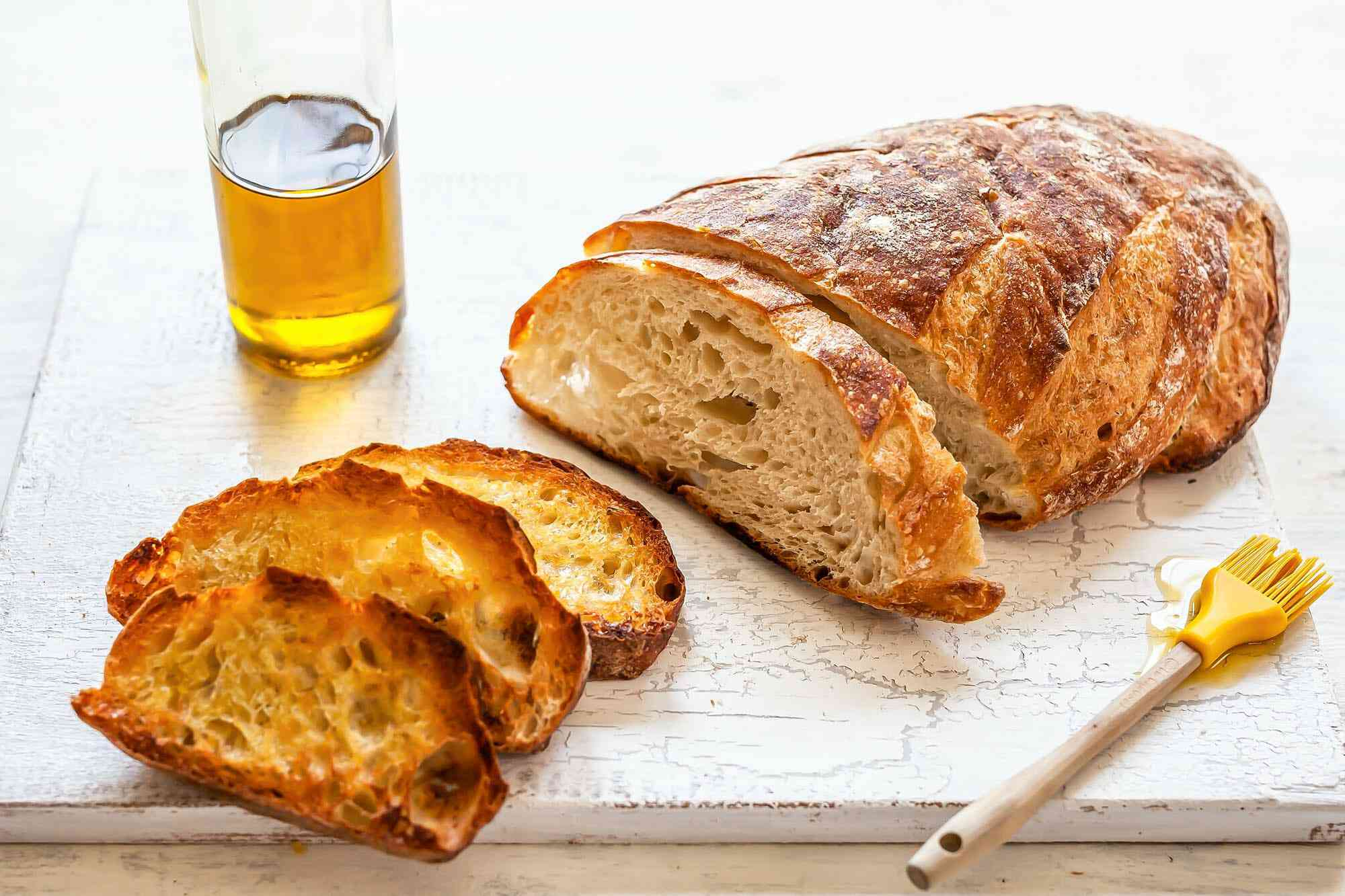 Sliced bread on a wooden board, a pastry brush, and a glass of olive oil. The first couple slices of bread are toasted.