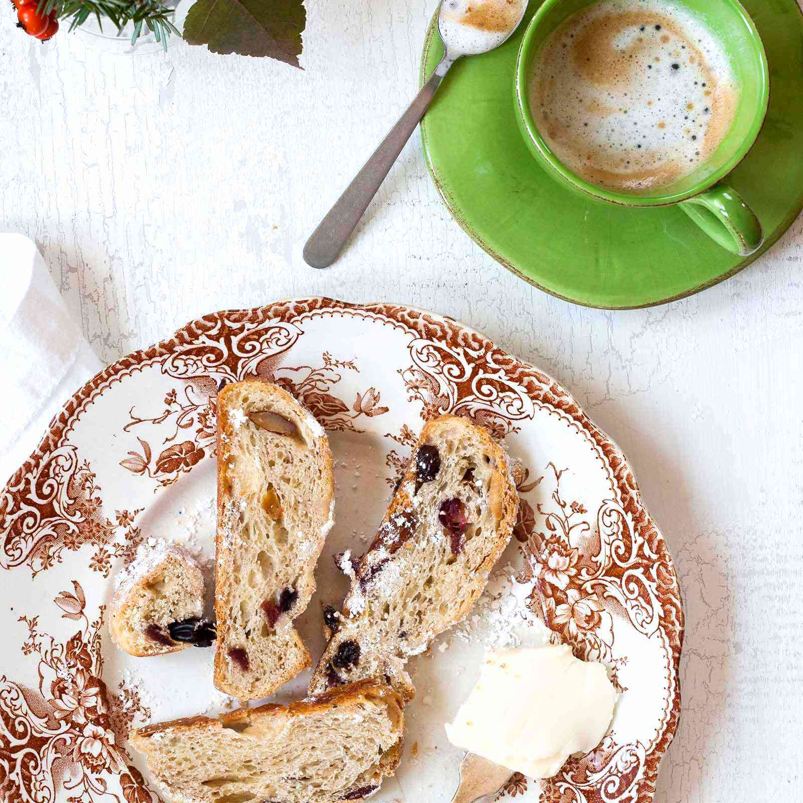 Stollen Christmas Bread filled with rum-soaked dried fruit coated with powdered sugar and sliced on a platter with a fine mesh sieve with powdered sugar and a cup of coffee in a green mug.