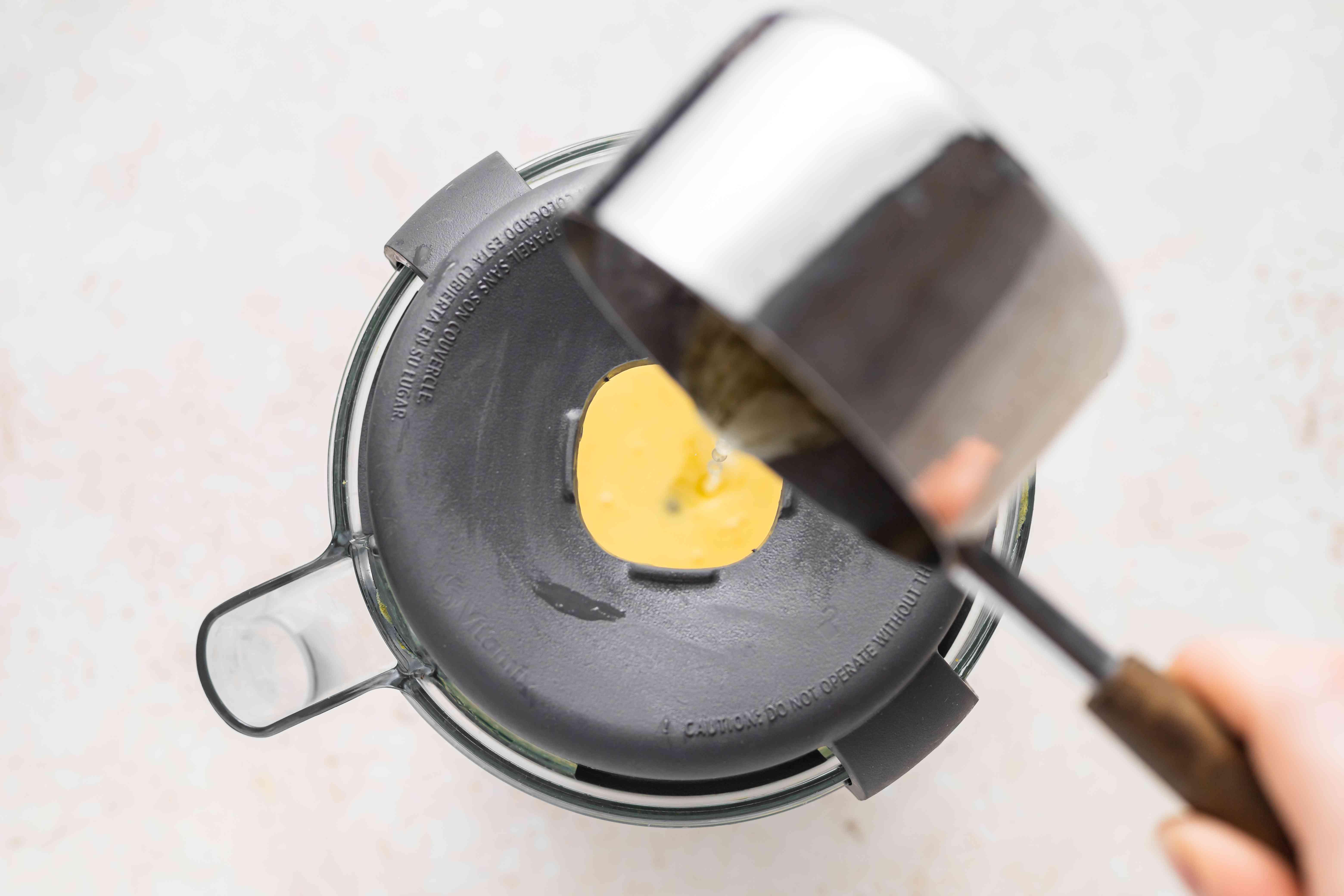 Drizzling melted butter in Blender Hollandaise Sauce.