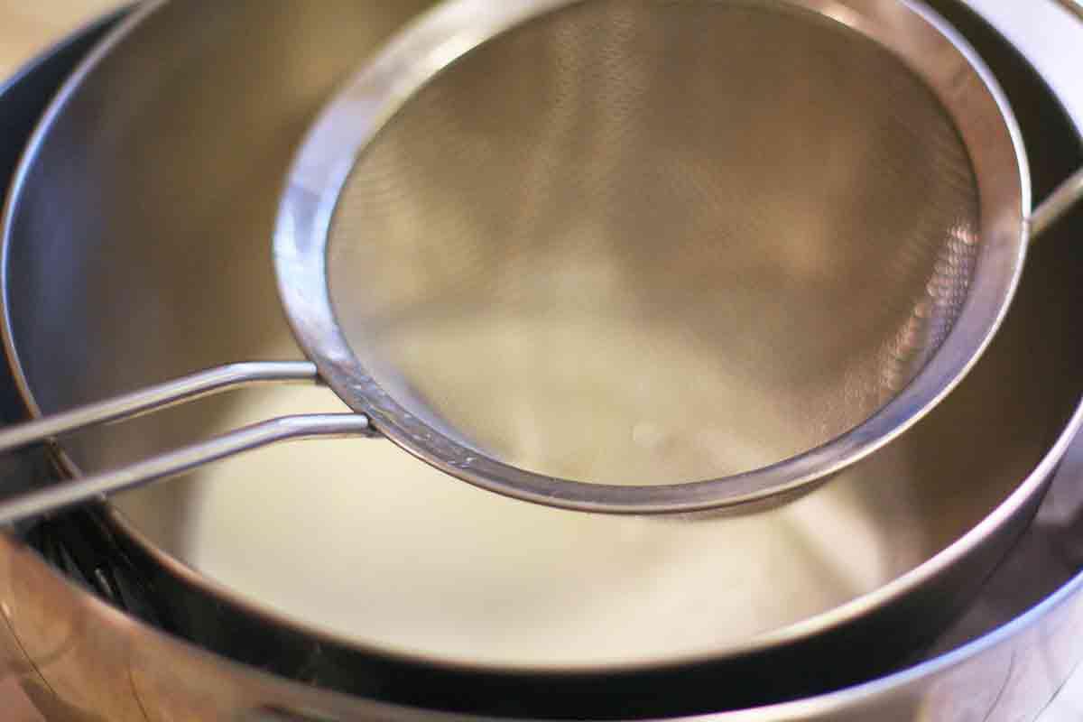 mesh strainer over the bowl of eggnog cream