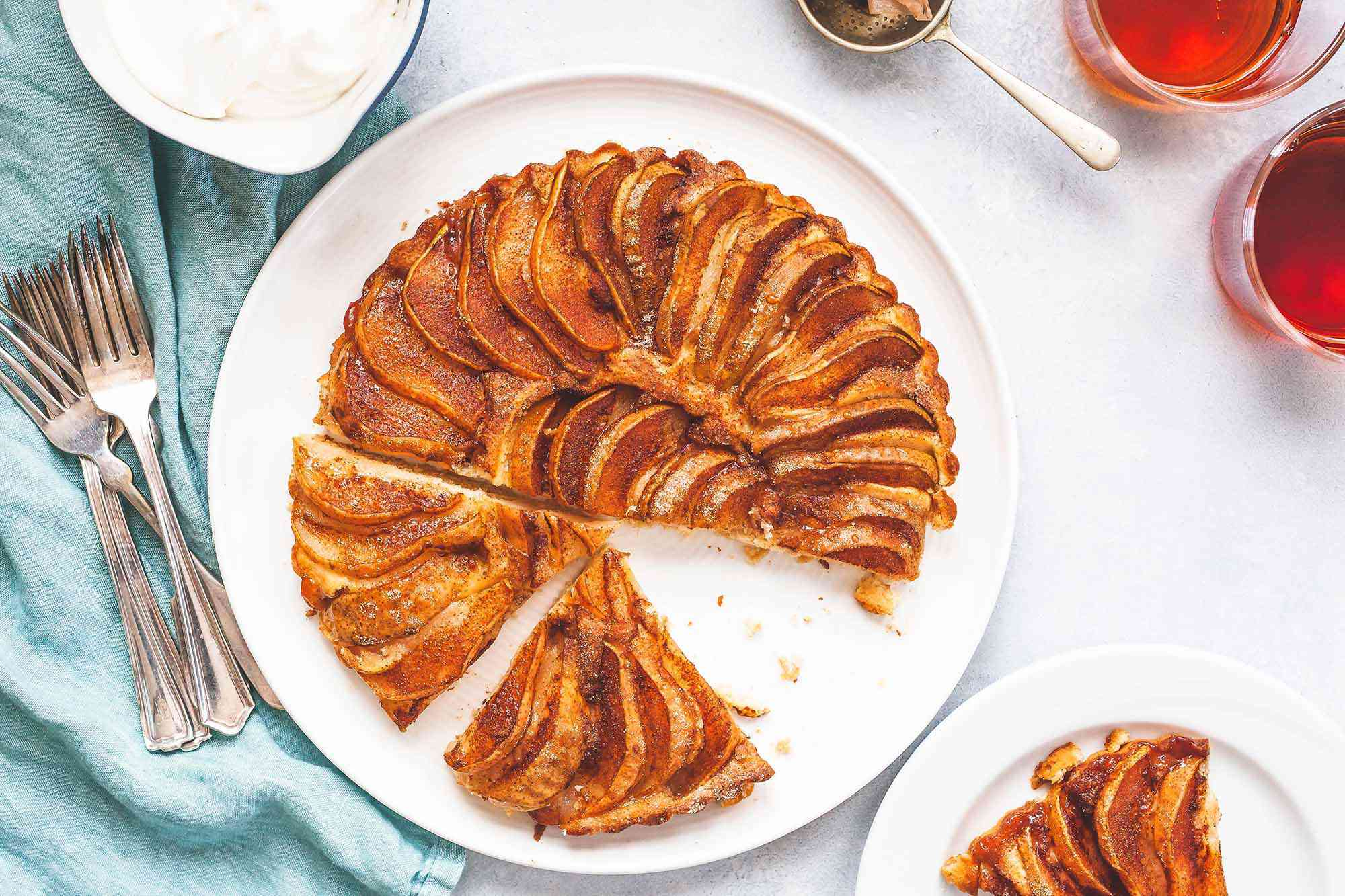 Pear cake with slices out on a plate.