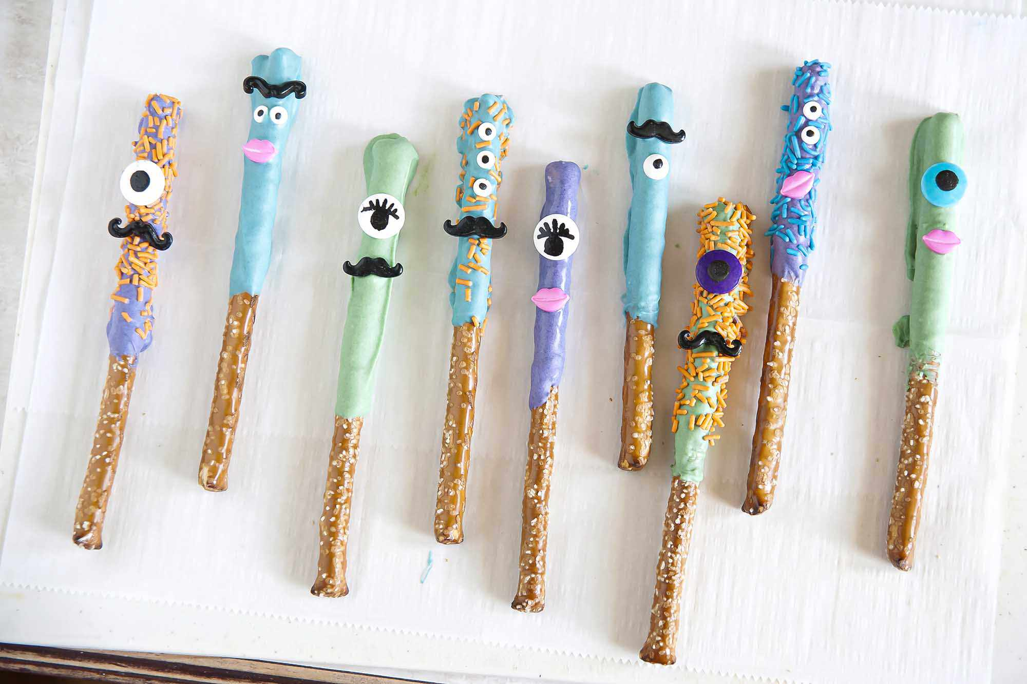 Homemade Chocolate dipped pretzel rods in blue, green and purple decorated with canyd eyes, mustaches and lips on a counter top.