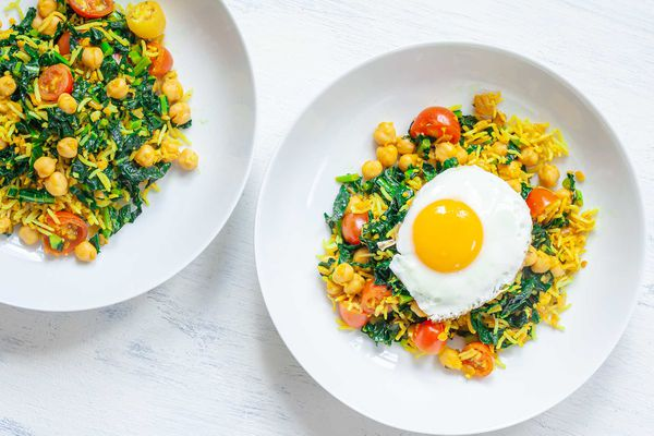 Overhead view of vegetable fried rice with turmeric with a fried egg on top and a fork in the bowl. A second bowl is to the left.