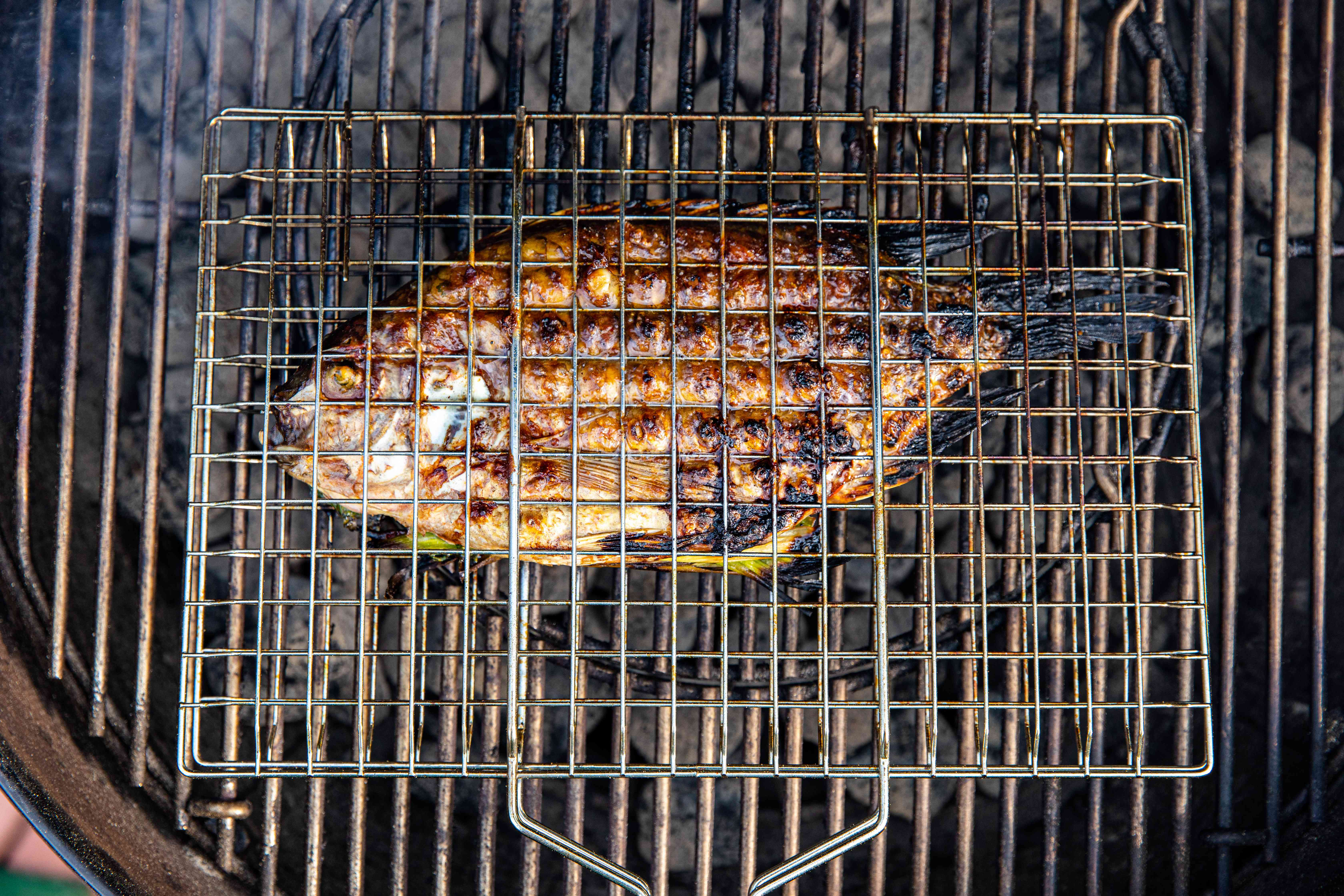 Whole fish stuffed with herbs and chilies on the grill.