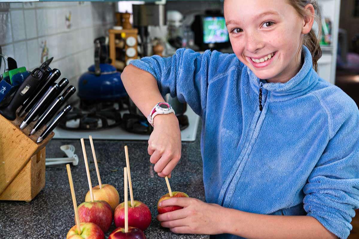 Caramel Apples Recipe putting sticks into apples
