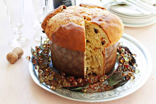 A loaf of homemade panettone in a paper mold with a slice cut out with a wreath around the base.