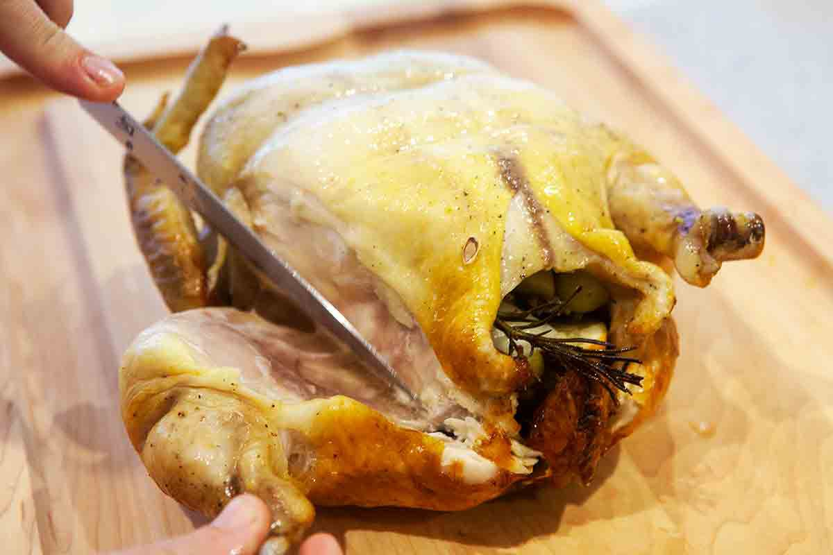 carve legs and thighs away from roast chicken with grapes