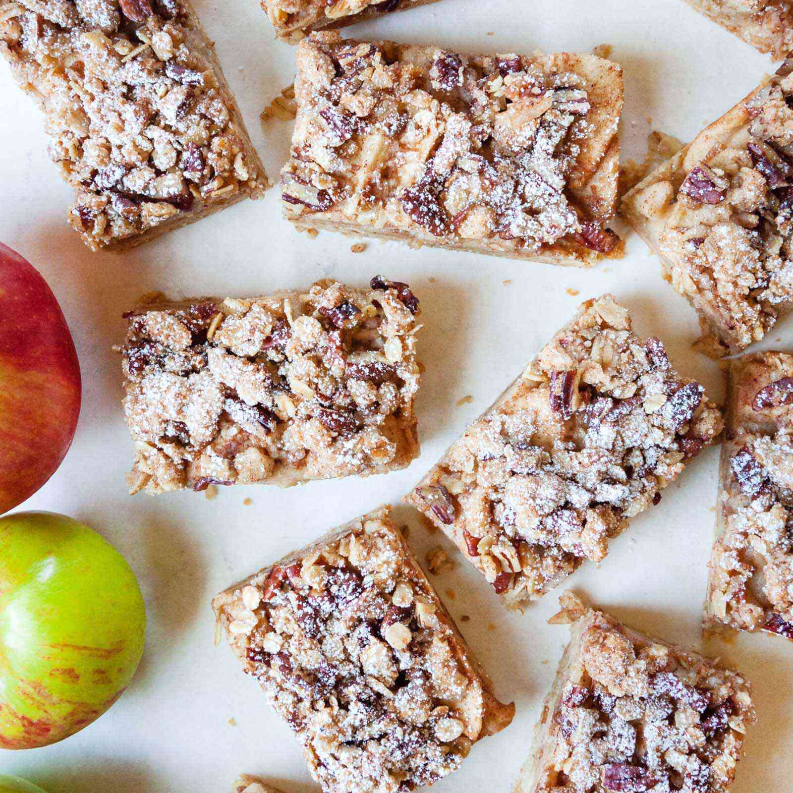 Easy apple pie bars cut into rectangles and set on a white background. Apples are in partial view to the left.