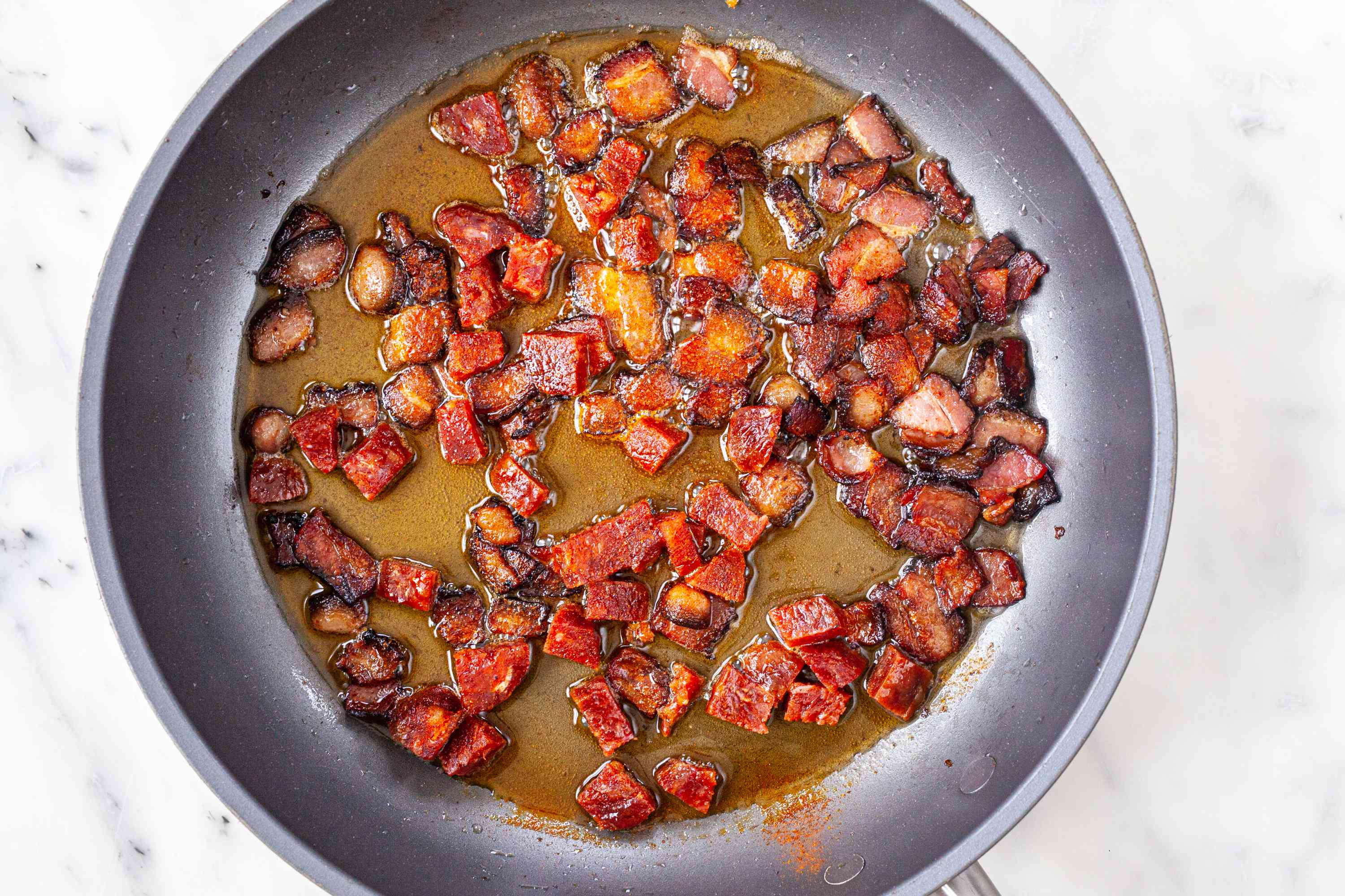Cooked chorizo and bacon in a skillet to make Spanish Style Migas.