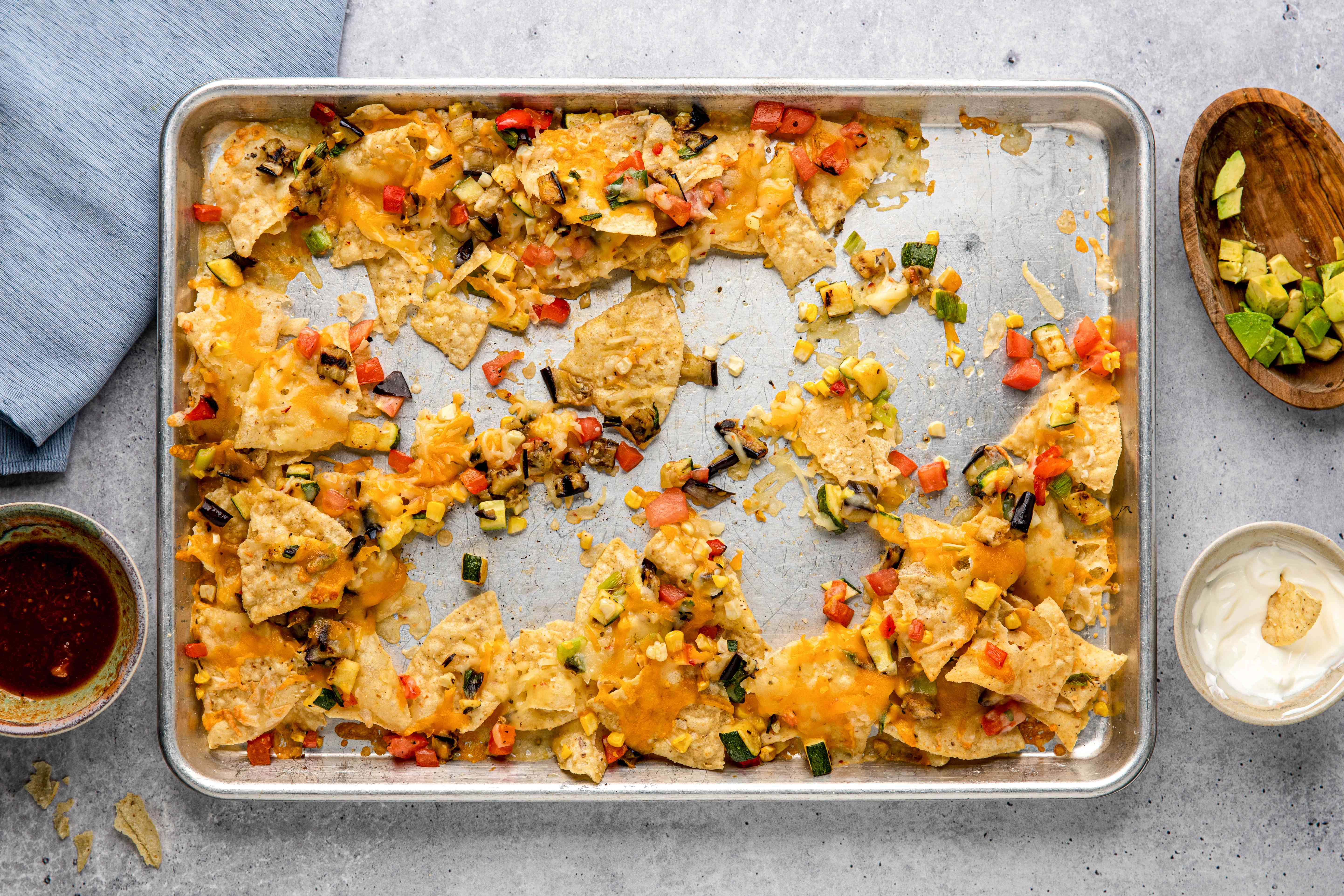 A baking sheet with half of the grilled summer vegetable nachos eaten.