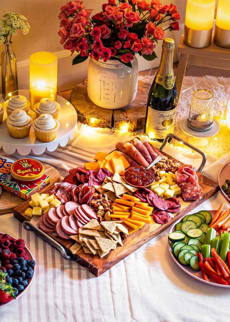 Meat and cheese board, fruit tray, heart shaped napkins, games, cupcakes, candles all layed out in Valentine's Day spread.