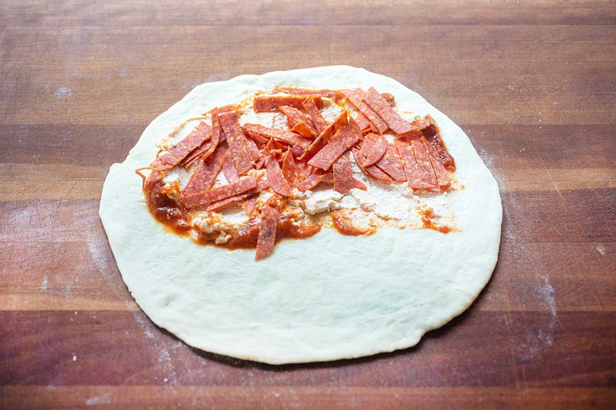Pepperoni Calzone topped with sauce and pepperoni