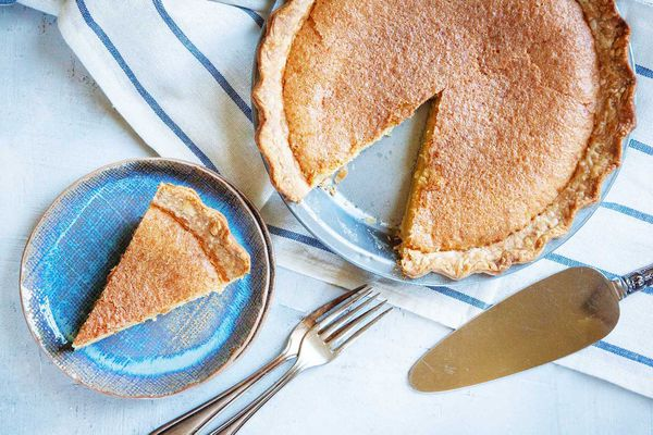 Overhead view of the best chess pie with a slice removed. The slice is on a blue plate with forks and a pie server to the right.