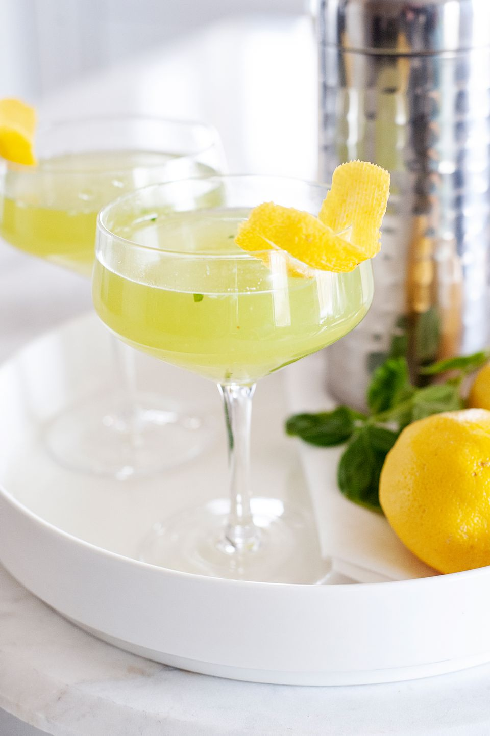 Side view of two Summery Garden Walk Cocktails on a white tray and garnished with lemon peels.