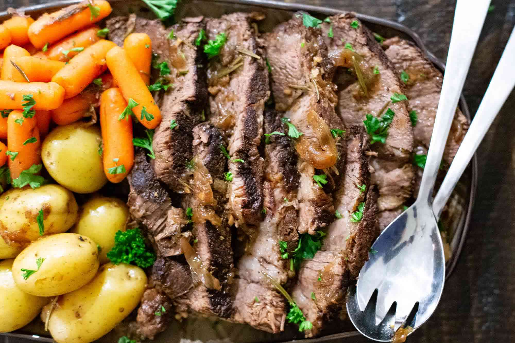 Instant Pot Pot Roast sliced and served on a platter with carrots and potatoes