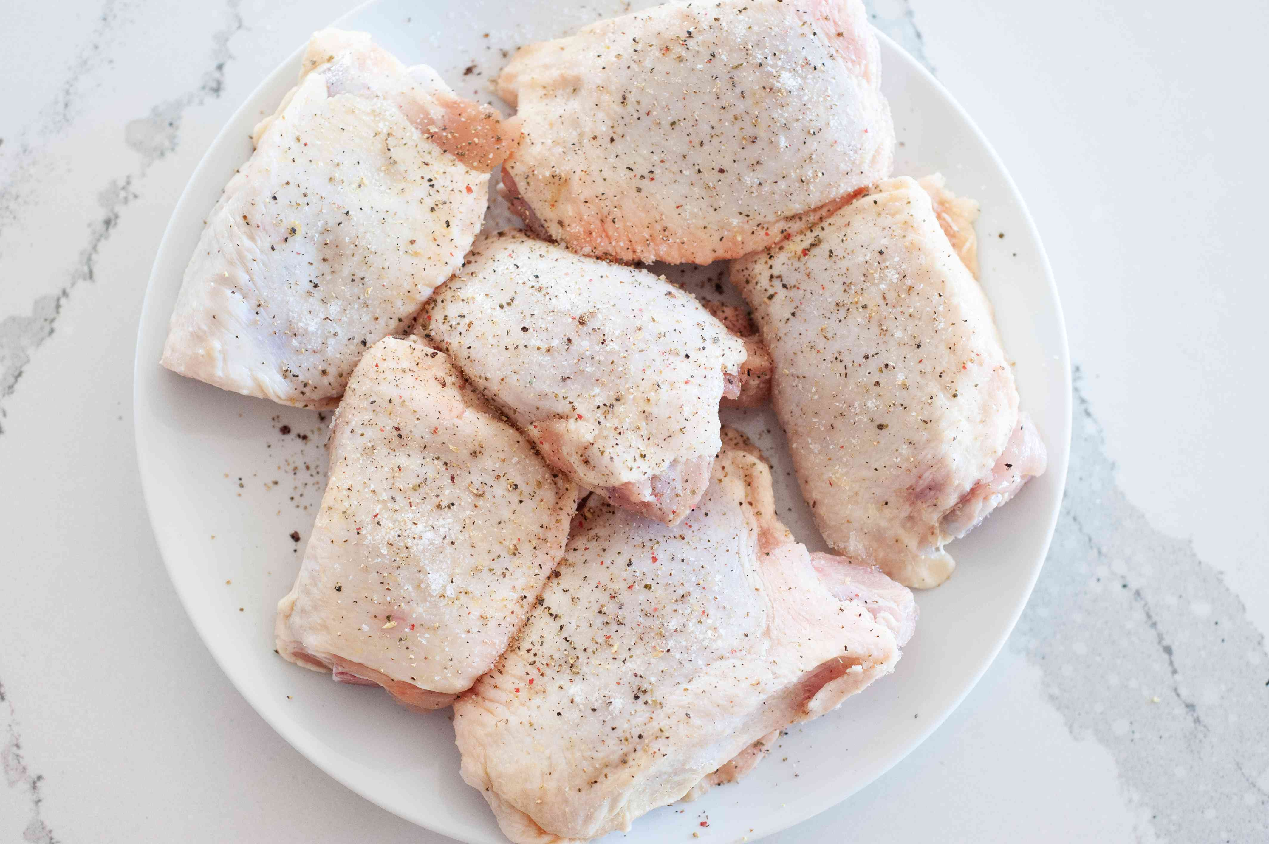 Seasoned chicken thighs on a plate for sheet pan chicken with vegetables.