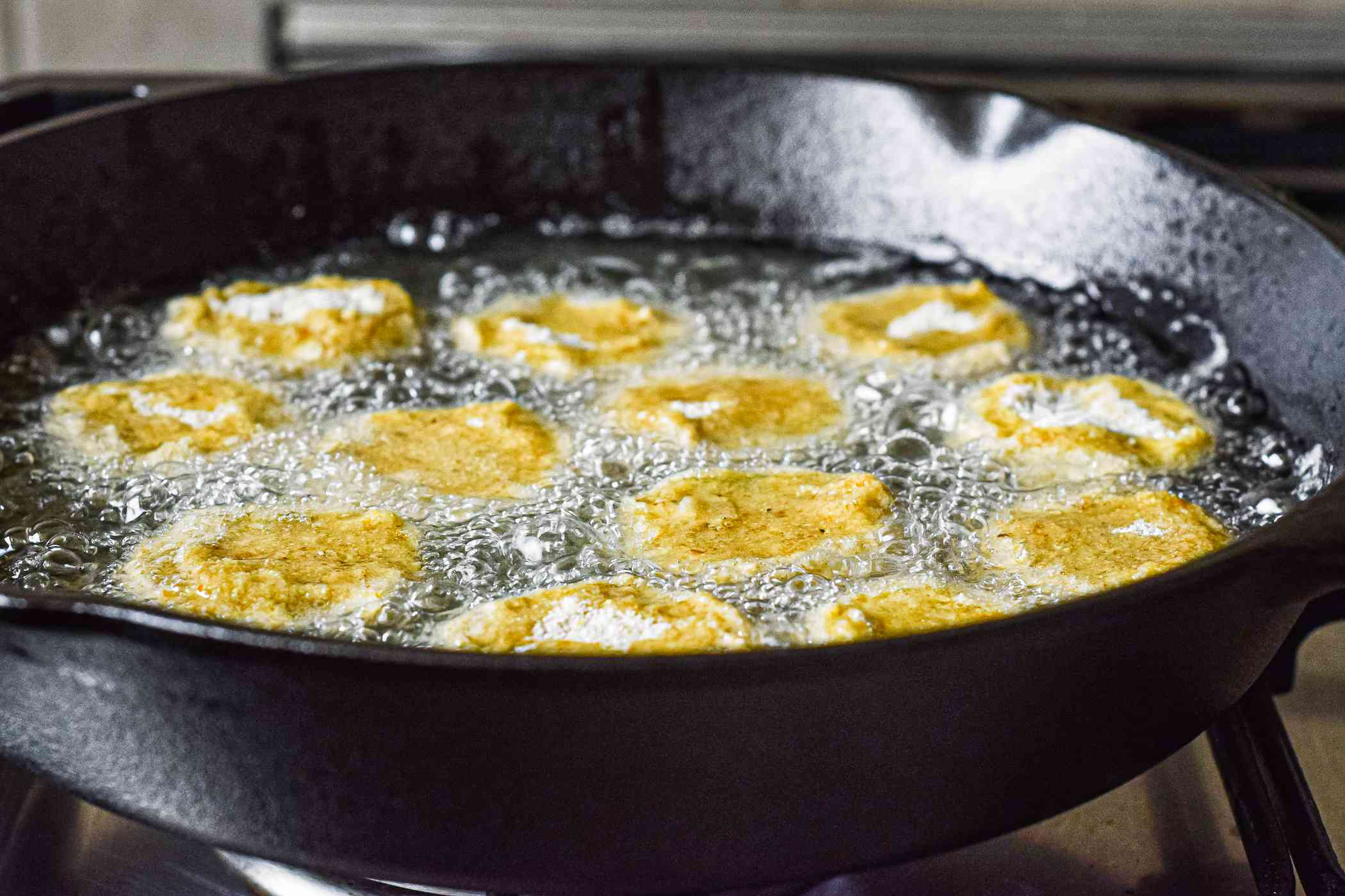 Frying green tomatoes in a cast iron skillet for fried green tomatoes.