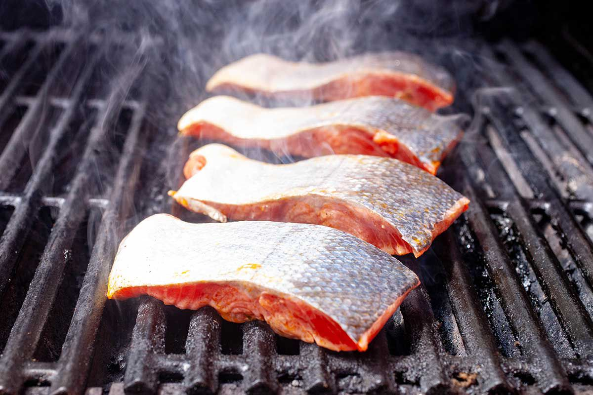 Grilled Salmon Fillet with Mango Salsa - four salmon fillets on a grill skin side up