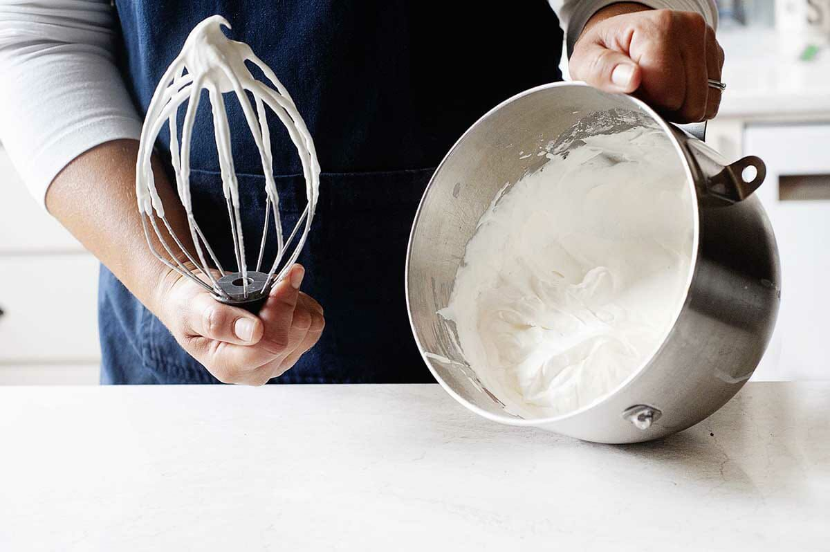 A person tipping the metal bowl of a stand mixer to show the whipped cream inside.