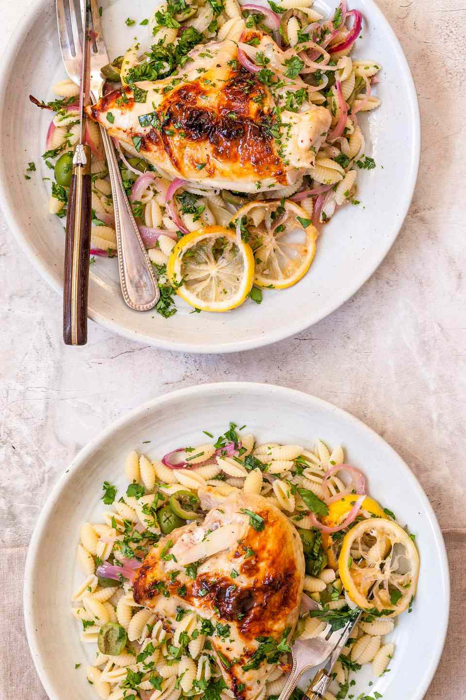 A vertical photo of two plates with easy weeknight chicken on each. Each plate has a golden brown roasted chicken breast, roasted lemon wedges, sliced red onion, shell pasta and herbs scattered over top. The top plate has a knife and fork on the left side of the plate. The bottom plate has the top of a fork visible on the bottom right corner.