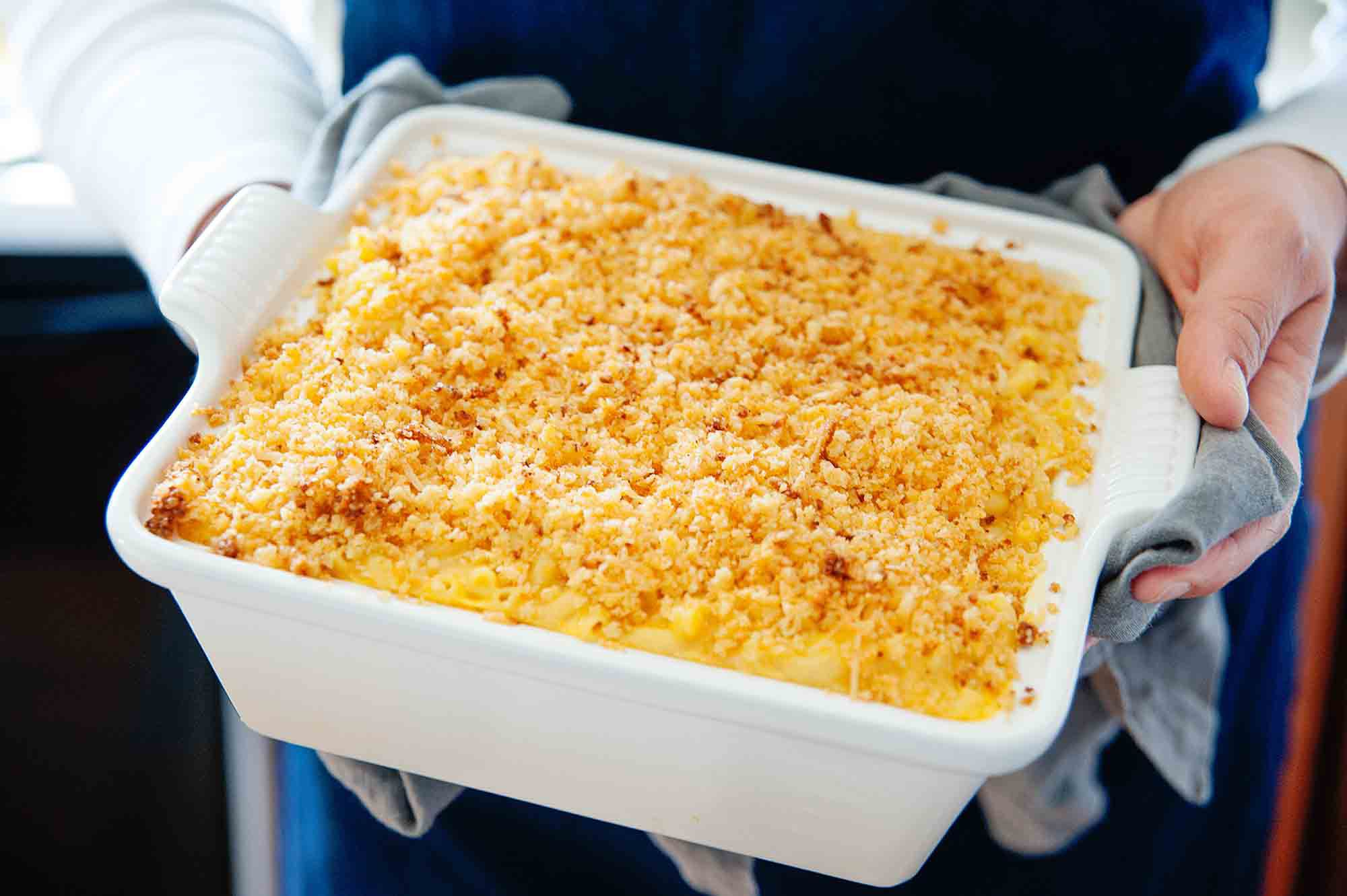 Kraft mac and cheese - woman's hands holding a white casserole dish filled with baked mac and cheese