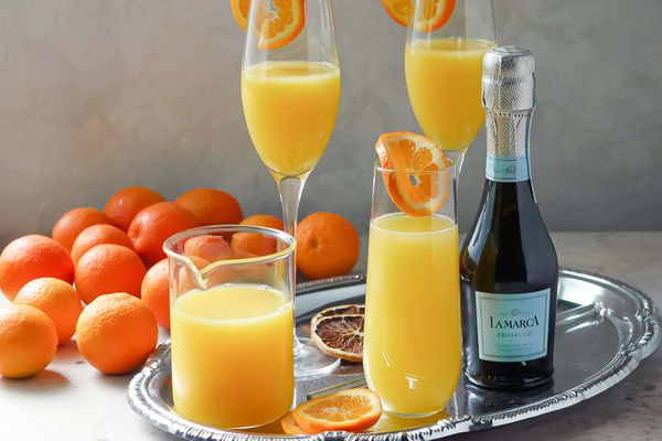 Prosecco, orange juice, orange slices and three glasses of the best mimosas are on a tray. Whole oranges are to the left of the tray.