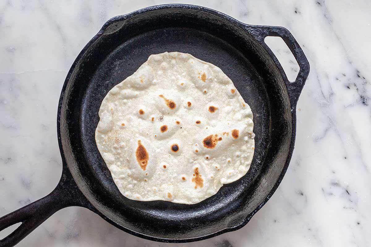 Flour tortilla cooking in a cast iron skillet on a marble countertop for a easy homemade flour tortilla.