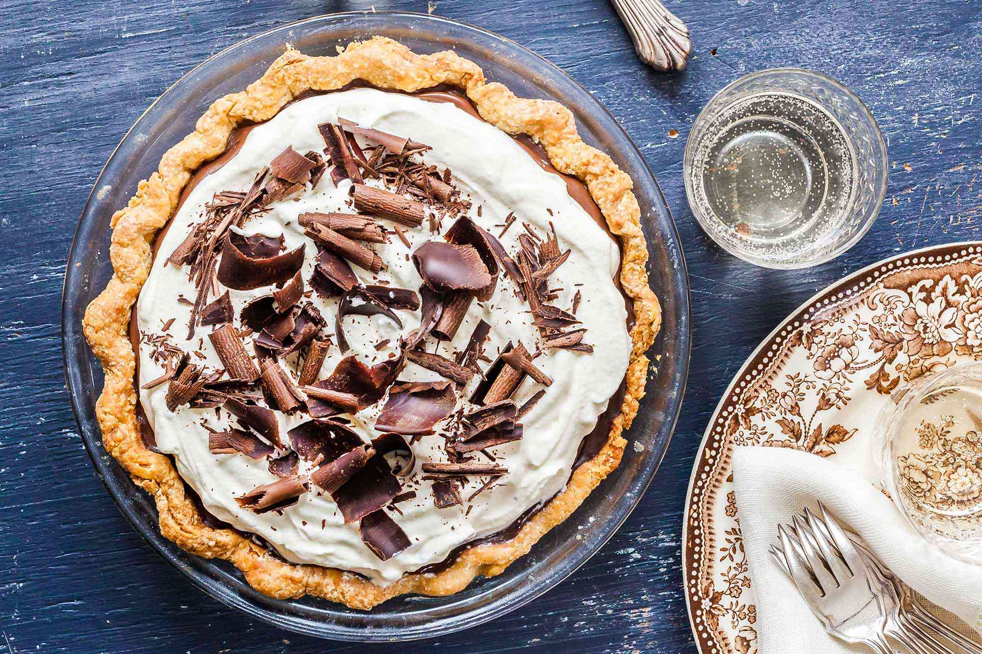 A whole chocolate pie topped with shaved chocolate.