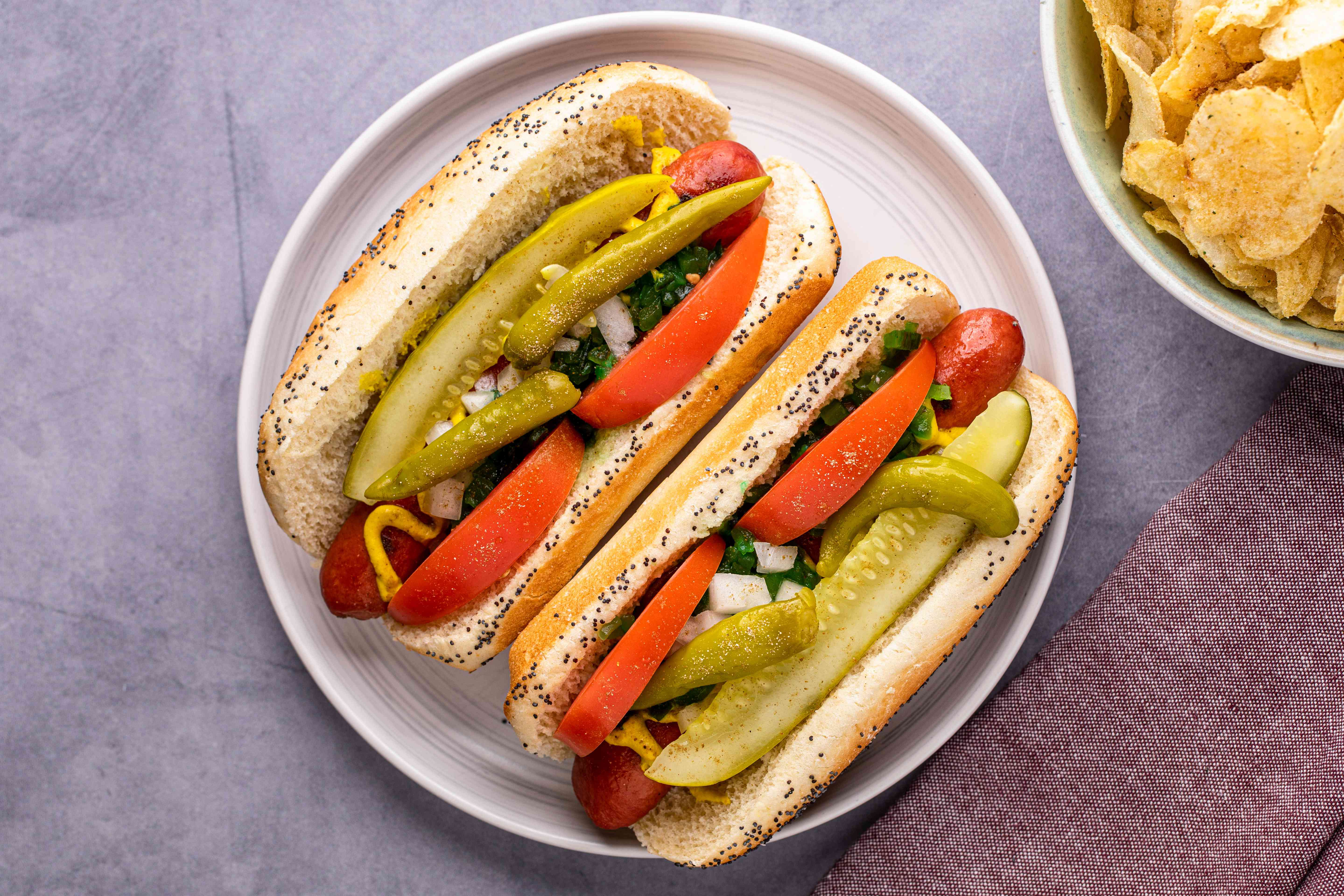 Overhead view of two Chicago dogs on a plate and topped with tomatoes and pickles.