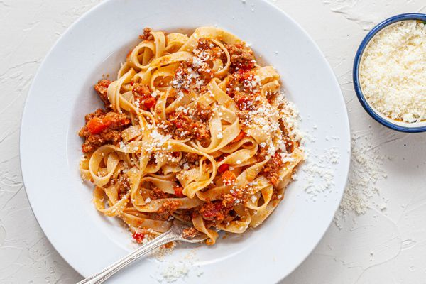 Pasta with bolognese sauce on a white plate.