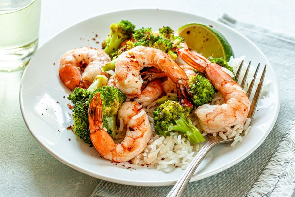 Spicy Honey Roasted Shrimp and Broccoli on a white plate with a fork.