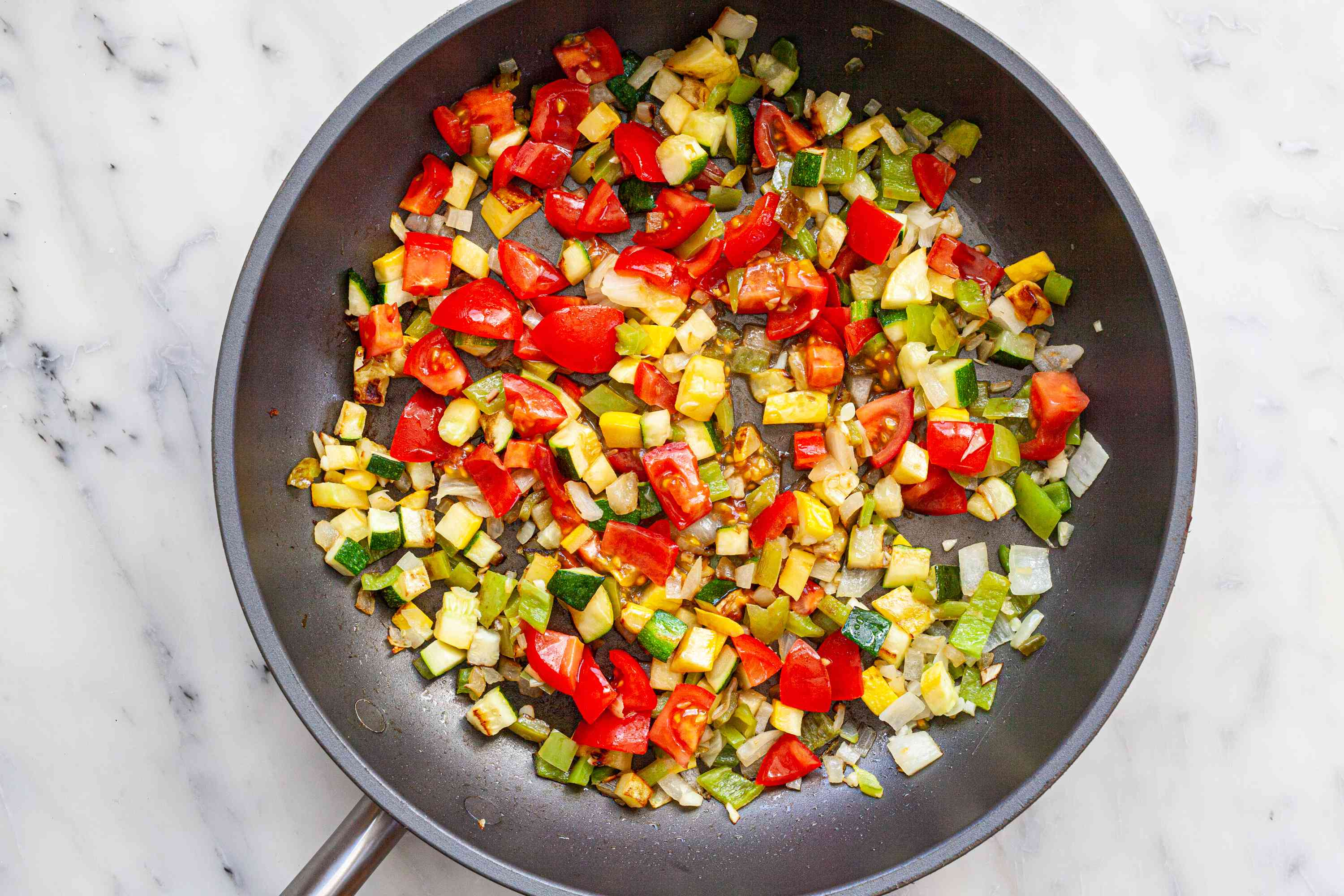 Diced vegetables in a skillet to show how to make tacos.