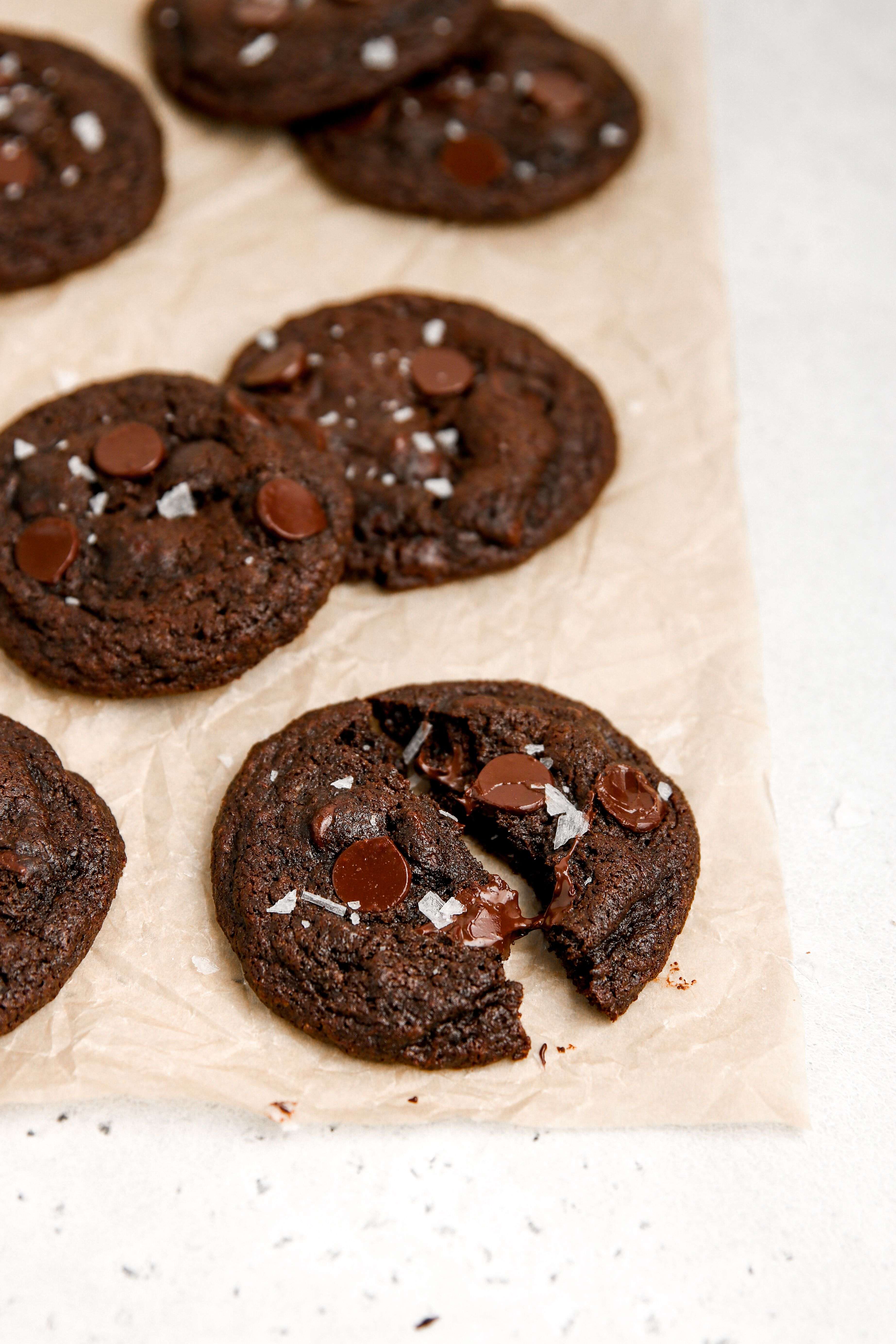 A baking sheet with chocolate chip chocolate cookies on it.