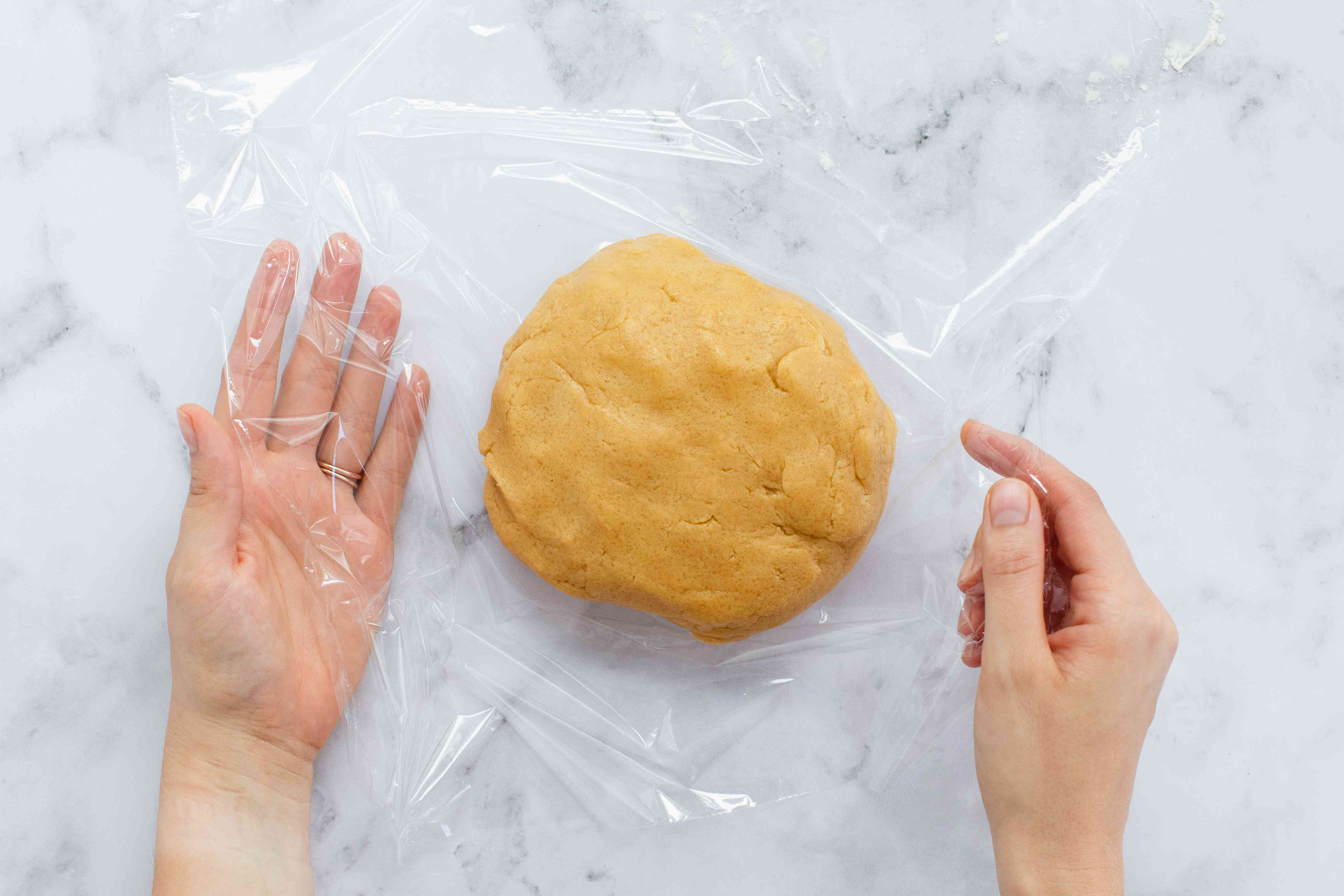Dough for Peanut Butter Cookies being wrapped in plastic wrap.