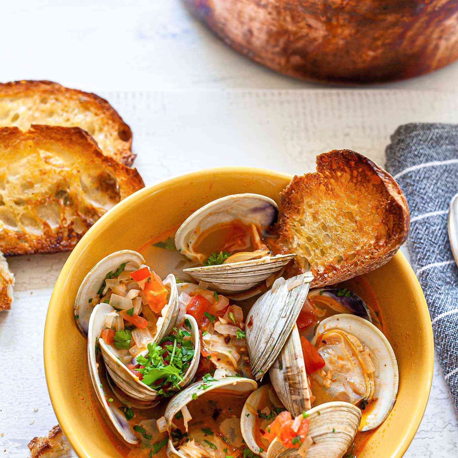 A yellow bowl of steamed clams with chorizo, grilled garlic bread and a stockpot of more brothy clams.