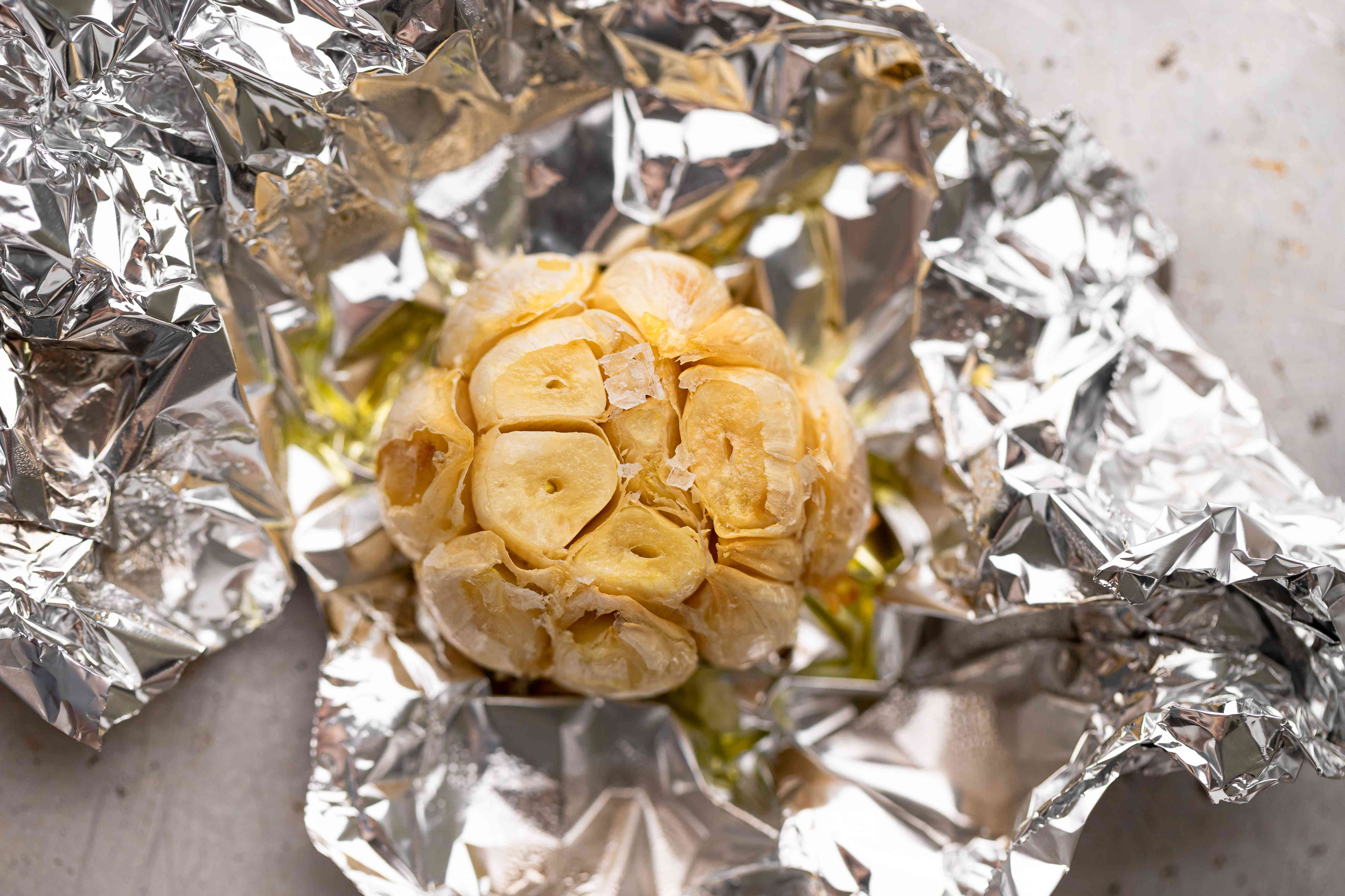 A roasted head of garlic in foil to make a garlic mashed potatoes recipe.