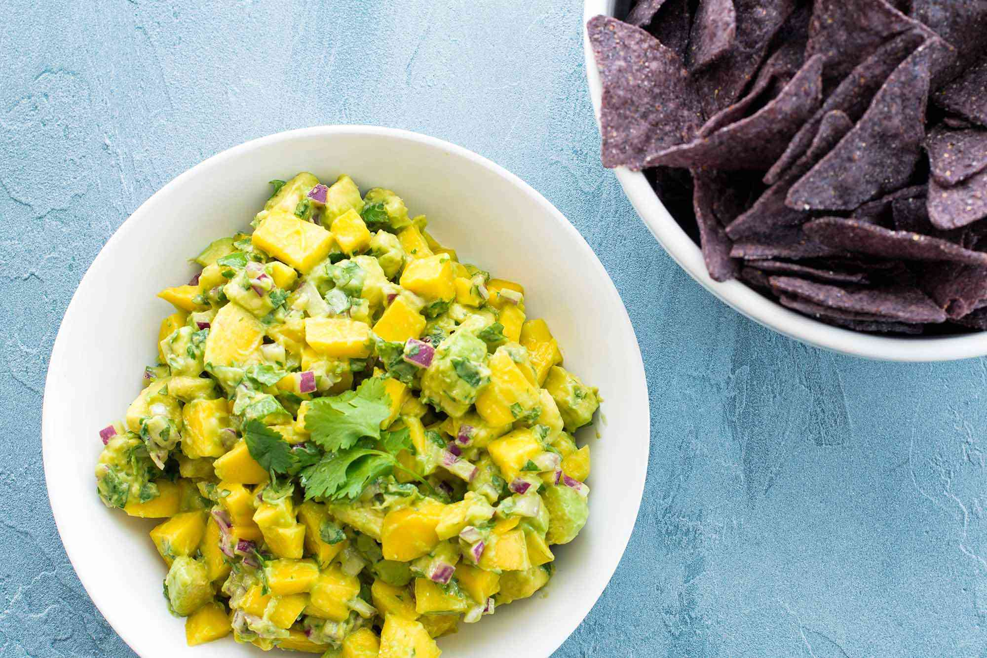 Salsa with Mangos and Avocado - - bowl of mangos and avocados with chips in the backgroun