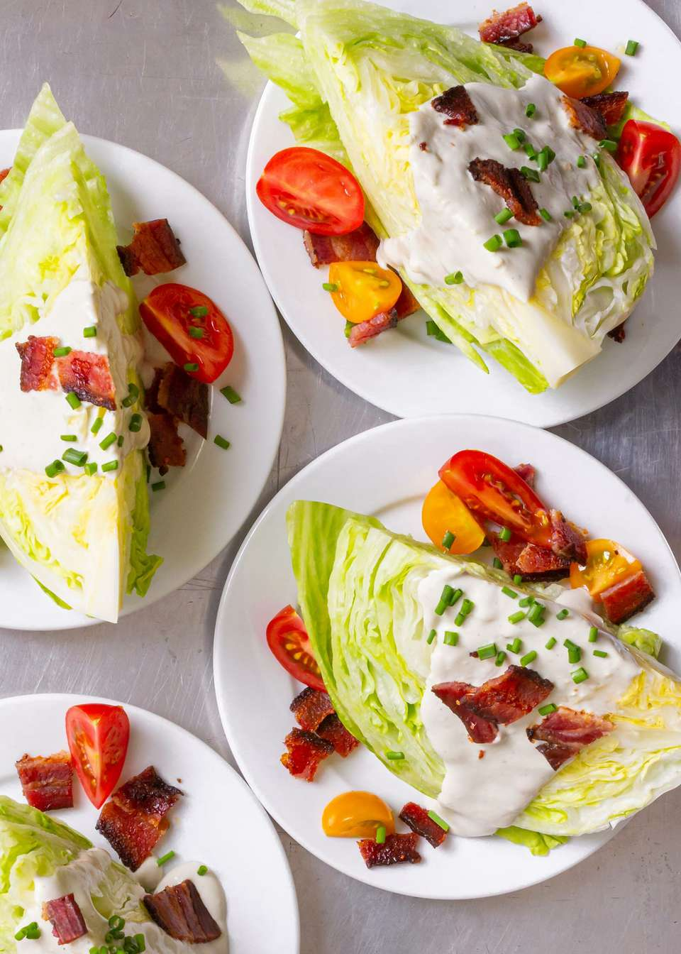 Iceberg wedge salads on white plates with blue cheese, bacon and tomatoes.