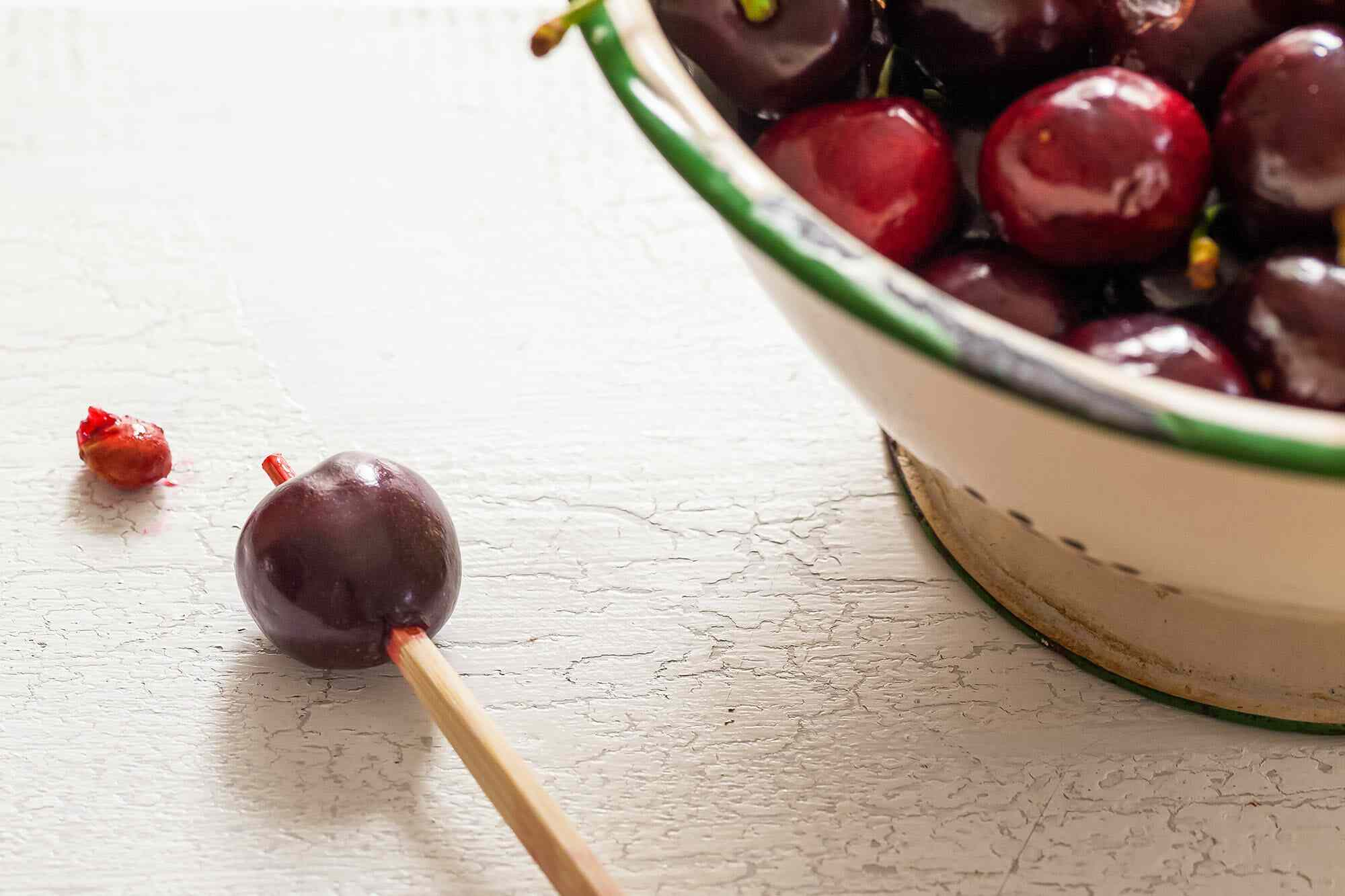 Best ways to pit cherries with a chopstick stuck through a red cherry with the pit laying next to it. A bowl of cherries is in partial view to the right.