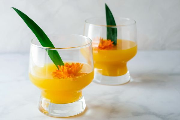 Two glasses of the best Pineapple-Mango Mimosa are on a marble counter. An orange flower and green pineapple leaf are inside each glass.