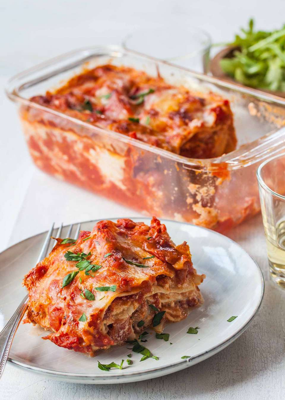 Vertical view of small batch of loaf pan lasagna with sausage on a plate garnished with chopped parsley and a fork on the left. Above the plate is the loaf pan with some of the lasagna missing. A partial view of a bowl of lettuce and a tumbler of white wine is visible.