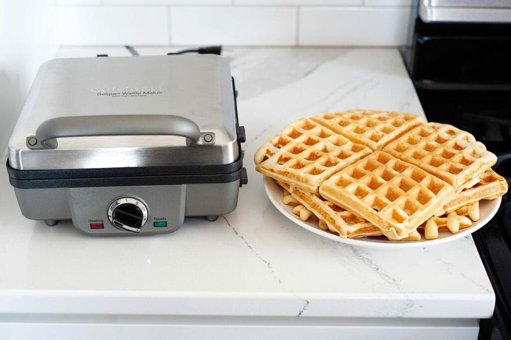 A stack of square waffles on a plate next to a closed waffle maker sitting on a counter.