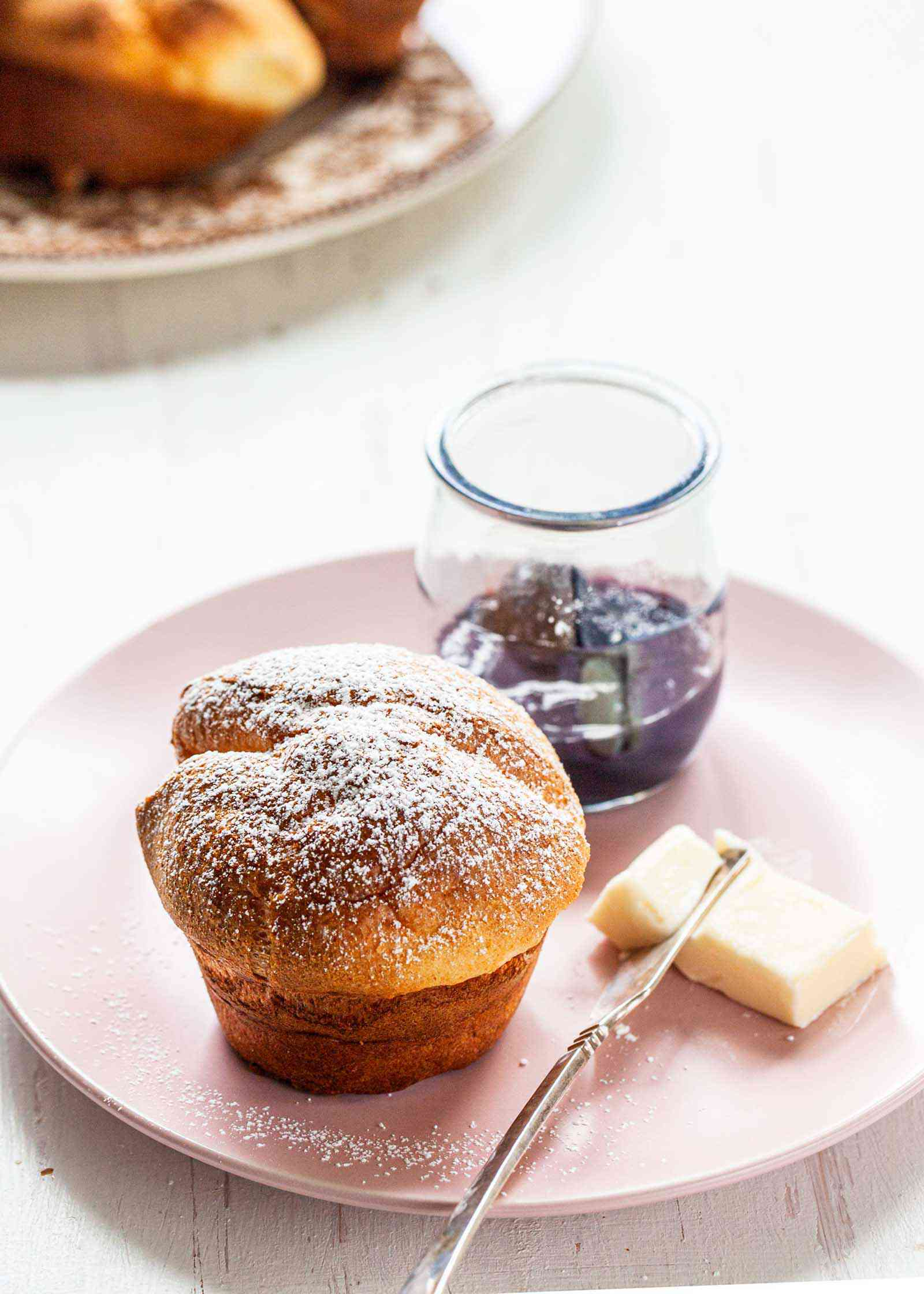 A popover on a plate with a pat of butter and jelly jar.
