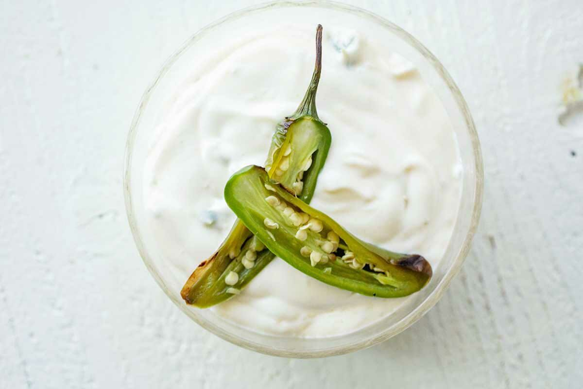 Roasted serrano pepper sliced on top a bowl of mayo to make topping for homemade BBQ Chicken Sandwiches.